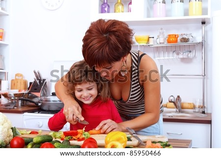Mother helping daughter in the kitchen - stock photo