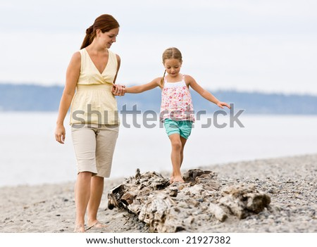 Mother helping daughter walk on log at beach - stock photo