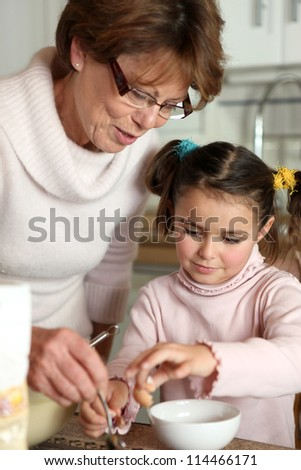 Mother helping daughter with boiled egg - stock photo