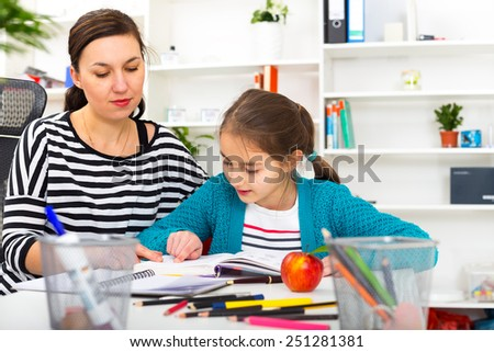 Mother Helping Daughter With Homework.  - stock photo