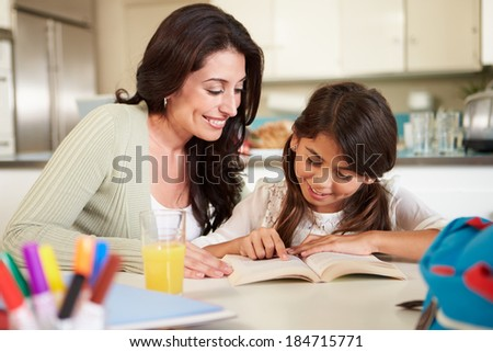 Mother Helping Daughter With Reading Homework At Table - stock photo