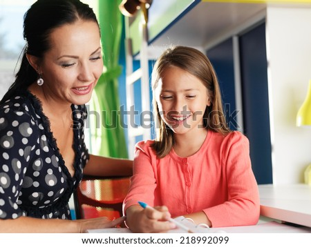 mother helping happy daughter with homework - stock photo