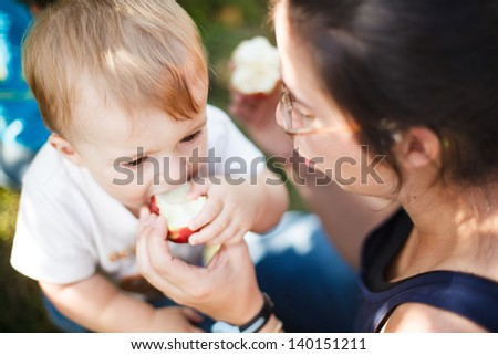 Mother helping her baby eat an apple - stock photo