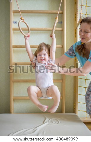 Mother helping her baby to play sports on the gym equipment. - stock photo