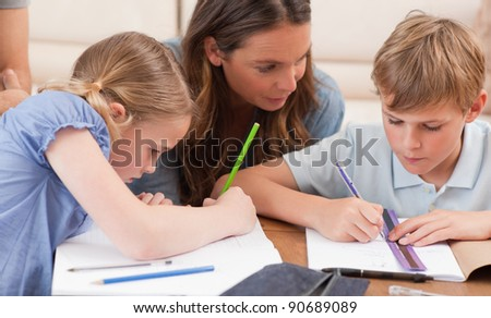 Mother helping her children to do their homework in a living room - stock photo