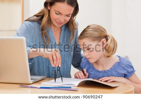 Mother helping her daughter doing her homework in a kitchen