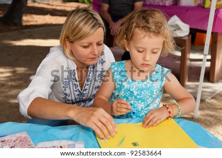 Mother helping her daughter during her art activities. - stock photo