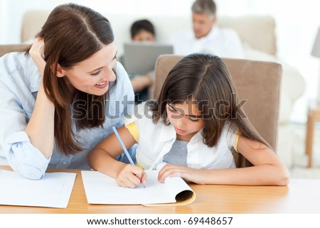 Mother helping her daughter for her homework - stock photo