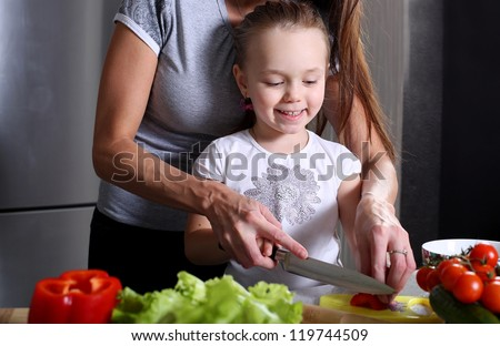 mother helping her daughter prepare salad in the kitchen - stock photo