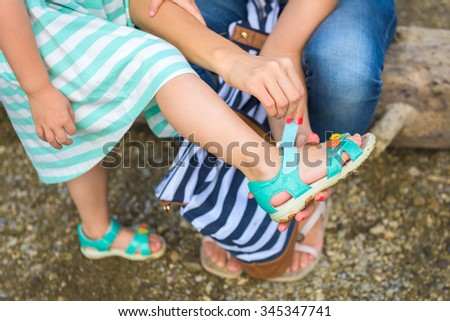 Mother helping her daughter to put on summer sandals - stock photo