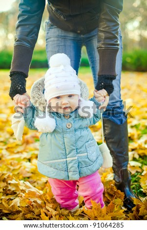 mother helping her daughter with her first steps in the park in autumn - stock photo