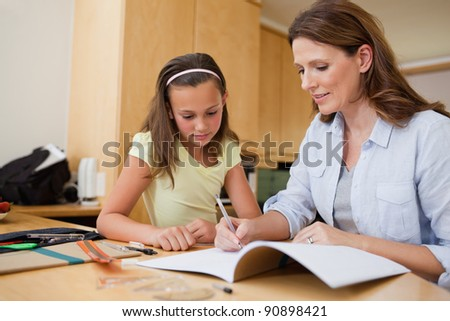 Mother helping her daughter with her homework - stock photo