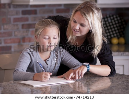 Mother helping her daughter with homework - stock photo