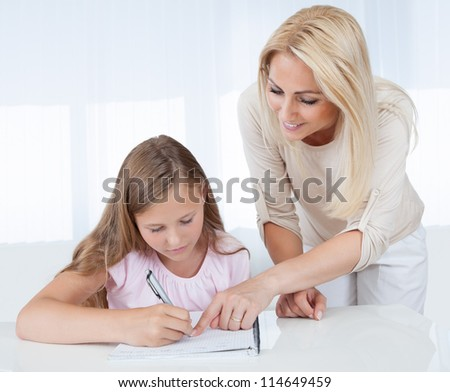 Mother Helping Her Daughter With Homework At Home - stock photo