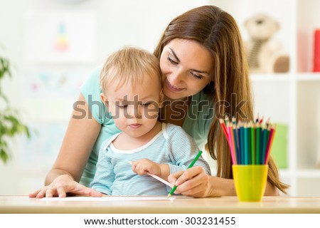 Mother helping her kid son to make drawings - stock photo