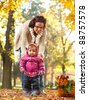 Mother helping her little child to walk on a nice autumn day - stock photo