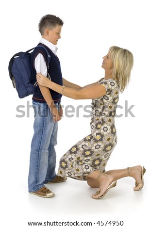 Mother helping her's young son prepare to school. Isolated on white in studio. Side view, whole body - stock photo