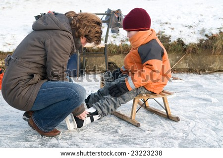 Mother helping her son putting on his ice skates - stock photo