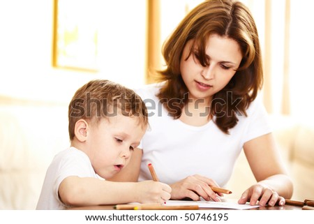mother helping in homework to her son; indoor - stock photo