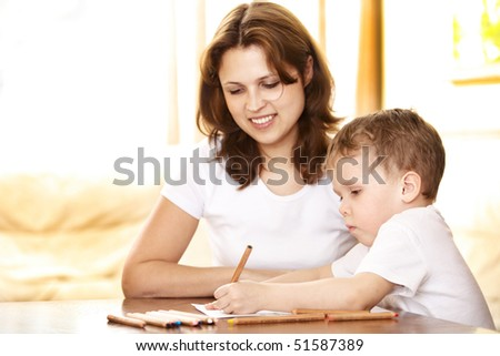 mother helping in homework to her son; shallow DOF, focus on boy's eyes - stock photo