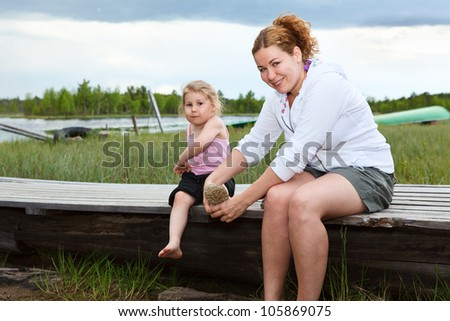 Mother helping small daughter to wear boots on river