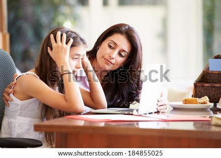 Mother Helping Stressed Teenage Daughter Looking At Laptop - stock photo