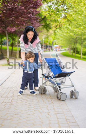 Mother helping toddler boy to pushing  his pram in park - stock photo