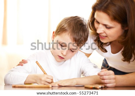 mother helping with homework to her son indoor - stock photo