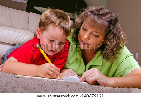 Mother helping young son with his homework