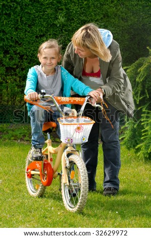 Mother helps daughter to ride on the bike - stock photo