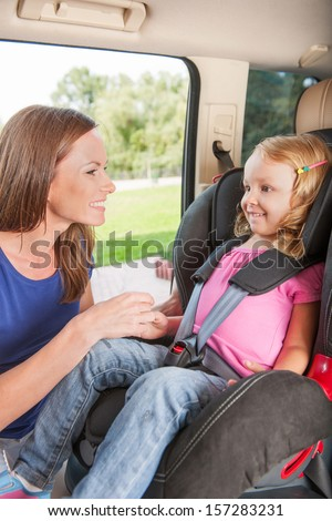 Mother helps her daughter to fasten belt on car seat - stock photo