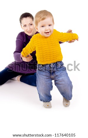 mother helps to do the first steps of the child isolated on white background - stock photo