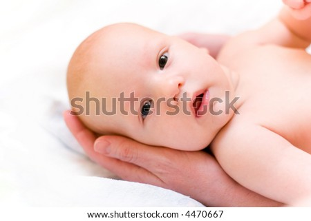 Mother hold baby in hands. Baby look at camera - stock photo