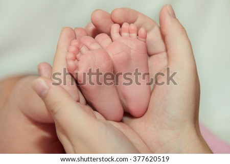 mother hold feet of newborn baby. Newborn baby peacefully sleeping.Adorable beautiful newborn baby girl. Maternity and newborn concept. - stock photo