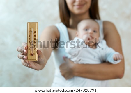 mother holding a baby and shows on the air temperature thermometer - stock photo