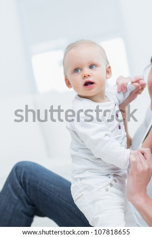 Mother holding a baby by his hands in living room