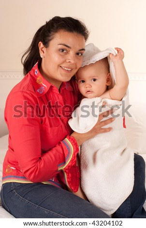 Mother holding a baby wrapped in a bath towel - stock photo