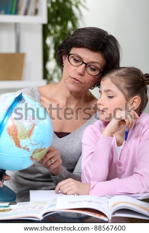 mother holding a globe and giving explanations to her daughter - stock photo