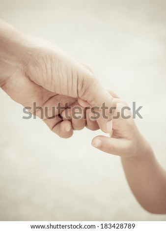 Mother holding a hand of child - stock photo