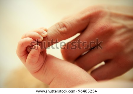 Mother holding a hand of his baby - stock photo