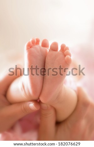 Mother holding a little pink baby feet