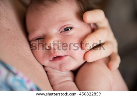 mother holding a newborn baby looking at the camera - stock photo