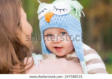 Mother holding adorable little baby in a cute hat outdoor - stock photo