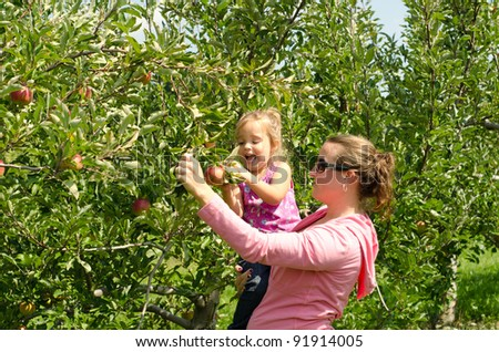 Mother holding an excited girl picking an apple - stock photo