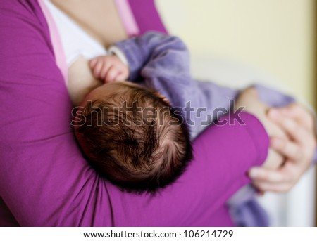 Mother holding and feeding newborn baby,rear view. - stock photo