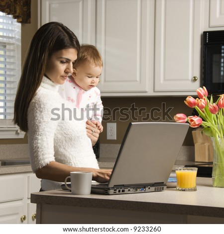 Mother holding baby  and typing on laptop computer in kitchen. - stock photo