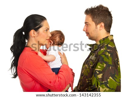 Mother holding baby boy and talking with her military husband isolated on white background