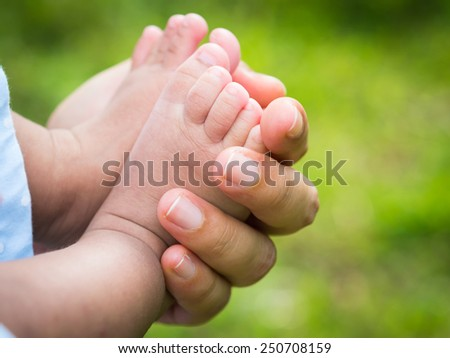 mother holding baby feet with natural background - stock photo