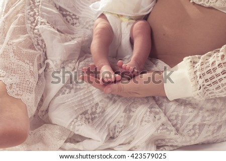 Mother holding baby foot in your lap