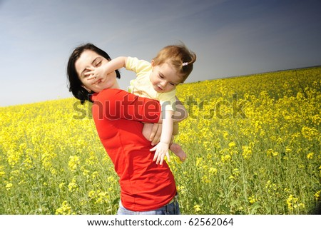 Mother holding baby girl in a rapeseed field - stock photo